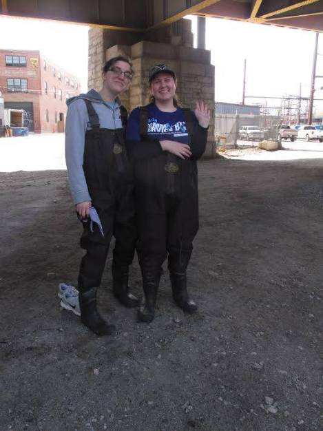 Christine Wertz and a fellow UB student in protective waders, ready to get in the Jones Falls and pull trash out - during Community Ser- vice Day, Spring 2014.