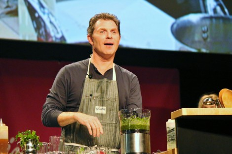 While demonstrating his talents, Bobby Flay interacts with the audience