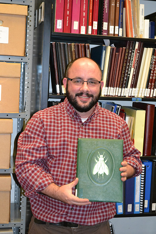 Archivist Aiden Faust with a 1950s UB yearbook Photo courtesy of Laura Melamed