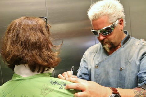 Backstage, Guy Fieri signs a fellow chef's jacket at a mix and mingle event available to the public with the purchase of a VIP ticket.