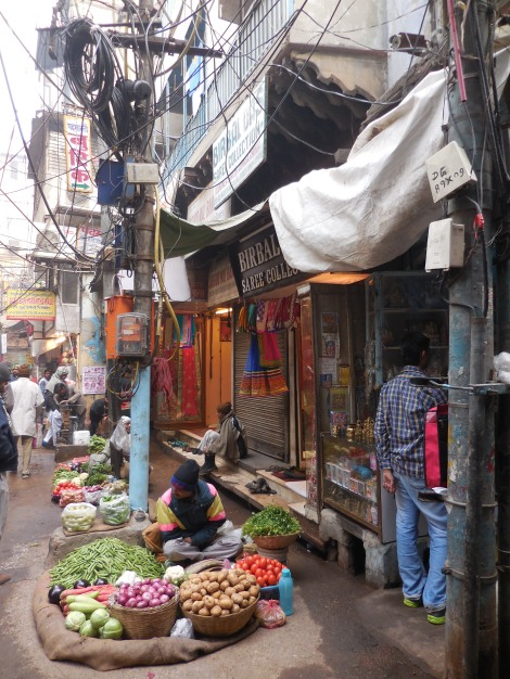 Vendors sell their wares along a street in Old Delhi. The tangle of wires above them are not defunct; electricians in Delhi know perfectly well where each one leads.