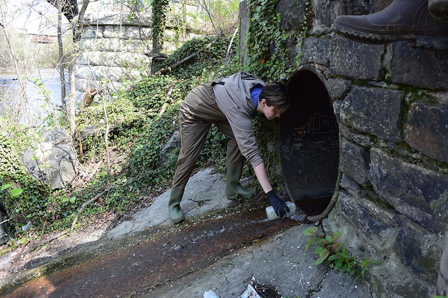 Harris takes water samples at the Jones Falls.