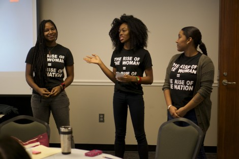 The Women of Color Student Association runs a new meeting while all standing up in unison.